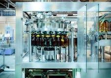 Машина завалки льет пиво в пластичные бутылки ЛЮБИМЧИКА Стоковая Фотография