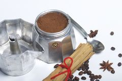 Машина кофе гейзера стоит на таблице, заполненной с земным кофе Рядом на лож таблицы зерна кофе и специй: c Стоковые Изображения RF