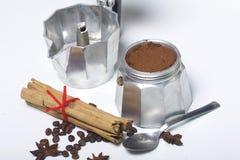 Машина кофе гейзера стоит на таблице, заполненной с земным кофе Рядом на лож таблицы зерна кофе и специй: c Стоковая Фотография RF