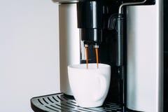 Машина кофе подготавливая свежий кофе и лить в чашку Стоковые Фото