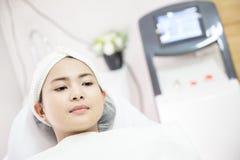 Машина лазера Молодая женщина получая обработку лазера прикладывать политуру кожи внимательности прозрачную Молодая женщина получ стоковые изображения rf