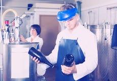 Машина мужского работника работая на фабрике игристого вина Стоковая Фотография