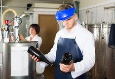 Машина мужского работника работая на фабрике игристого вина Стоковое Фото