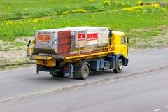Машина носит контейнеры багажа авиатранспортной компании эмиратов в международном аэропорте Pulkovo в Санкт-Петербурге, России Стоковое фото RF