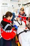 Машина скорой помощи помогая раненой женщине с вливанием Стоковые Изображения