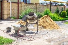 Машина смесителя цемента на строительной площадке, инструментах и песке стоковое фото rf