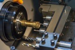 Машина токарного станка CNC сверля отверстие на латунной части вала стоковые изображения