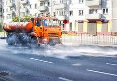 Машина чистки моя дорогу асфальта города с брызгом воды Стоковые Фото