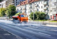Машина чистки моя дорогу асфальта города с брызгом воды Стоковые Фотографии RF