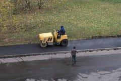 Машина compactor ролика приводов работника строительства дорог стоковое изображение rf