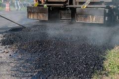 Машина paver асфальта работника работая во время строительства дорог Стоковые Изображения RF