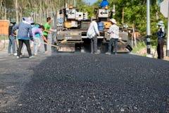 Машина paver асфальта работника работая во время строительства дорог Стоковые Фотографии RF