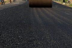 Машина paver асфальта работника работая во время строительства дорог Стоковая Фотография