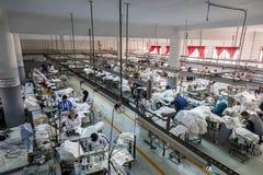 Машинист продукции фабрики ткани работая в линии стоковое изображение