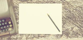 Машинка, карандаш и бумага на старом затрапезном деревянном столе Насмешка вверх Винтажное штейновое влияние стоковые фото