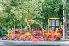 Машинное оборудование экскаватора на месте раскопк улицы окруженном с сетью безопасности конструкции подготовило для реконструкци Стоковые Изображения