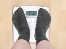 маштабы избыточного веса человека стоковая фотография