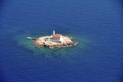 Маяк на малом утесе окруженном с морем сверху Стоковое Фото