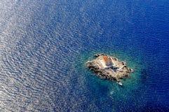 Маяк на малом утесе окруженном с морем сверху Стоковое Изображение