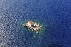 Маяк на малом утесе окруженном с морем сверху Стоковое фото RF