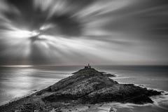Маяк на headland с солнцем испускает лучи над ландшафтом океана с стоковые фотографии rf