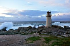 Маяк с волнами брызгая против утесов Дикое море с большими волнами и пеной Небо дождливого дня, захода солнца, голубых и красных  стоковое фото rf