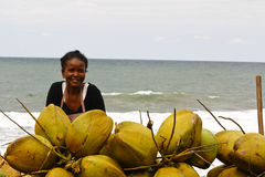 Малагасийская женщина продавая кокосы на пляже Стоковое фото RF