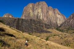 Малагасийские портеры под стороной скалы Tsaranoro. Стоковые Изображения