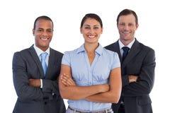 Малая группа в составе усмехаясь бизнесмены стоя совместно Стоковые Изображения RF