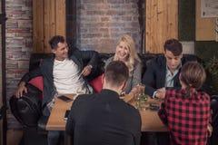 Малая группа людей, усаживание софы, таблица выпивает smartphones Стоковое Изображение
