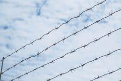 Малая глубина поля, старого колючего стального провода против голубого неба Стоковое Фото
