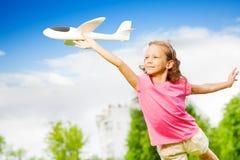 Малая девушка держит игрушку самолета с прямой рукой Стоковое Фото