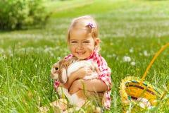 Малая девушка обнимая кролика в поле Стоковые Фотографии RF