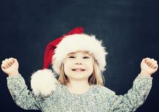 Малая девушка ребенка имея потеху 5 шлема рождества bou предпосылки лет santa портрета черного милого старых Стоковая Фотография