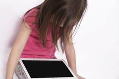 Малая девушка с планшетом на белой предпосылке Стоковые Изображения RF