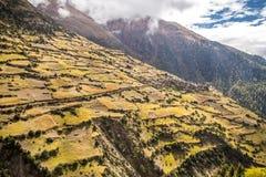 Малая деревня в горах, окруженных полями фермы Стоковые Фотографии RF