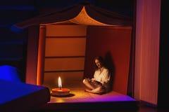 Малая книга чтения девушки в хате сделанной из книг Стоковая Фотография