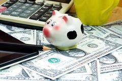Малая копилка и финансовый калькулятор, ПК таблетки на кучах  Стоковое Фото