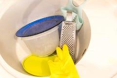 Малая куча пакостных блюд в кухонной раковине и желтых резиновых перчатках Стоковая Фотография