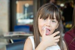 малая маленькая девочка лижет его пальцы стоковая фотография rf