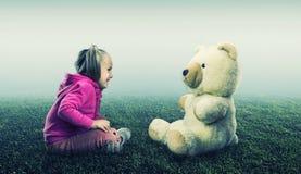 Малая милая девушка сидит и смотрит медведя игрушки Стоковые Изображения