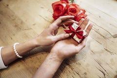Малая милая присутствующая коробка с смычком в красивых руках женщины Фокус на смычке Цветки красных роз позади на деревянном сто стоковое изображение