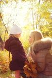 Малая дочь и ее мать смотря один другого и усмехаясь, счастливое детство, backlight в парке осени Стоковое Фото