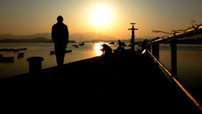 Малая пристань, тень человека на заходе солнца Стоковая Фотография RF