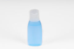 Малая пластичная бутылка пробирки заполнила при голубая жидкость изолированная над белой предпосылкой Стоковое Изображение