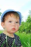 Малая, смешная девушка сидя в траве Стоковое Изображение