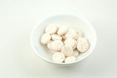 Малая тарелка содержа пилюльки витамин C Стоковая Фотография