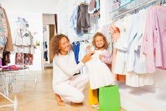 Малая усмехаясь девушка с красивыми покупками матери Стоковые Фотографии RF