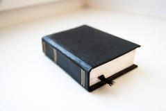 Малая черная книга при закладка лежа на белой поверхности Стоковое Изображение RF