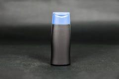 Малая черная пустая бутылка с голубой крышкой на темной предпосылке стоковые фото